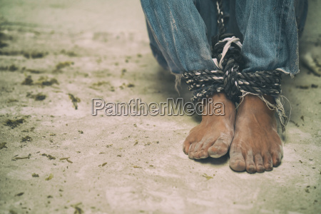 hopeless man feet tied together with