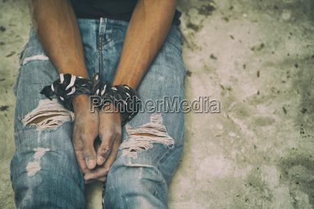 hopeless man hands tied together with