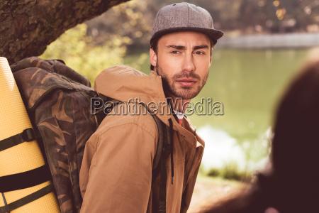 junger baertiger mann reisenden mit rucksack