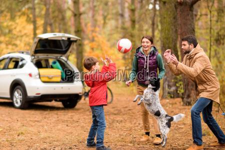 glueckliche familie mit ball spielen