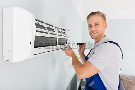 technician fixing air conditioner