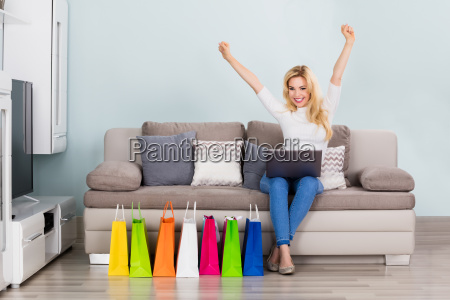 excited woman sitting on couch with