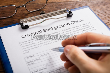 person filling criminal background check application