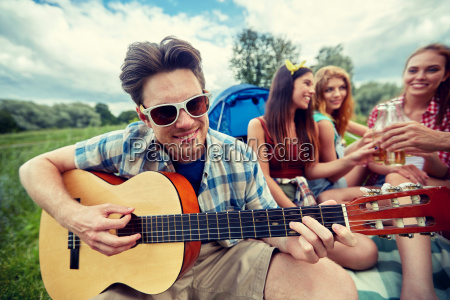happy man with friends playing guitar