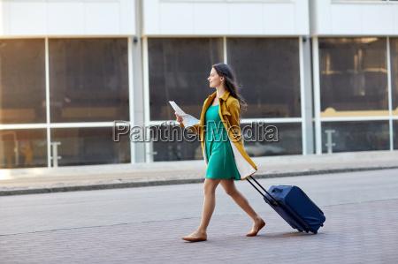 glueckliche junge frau mit reisetasche und