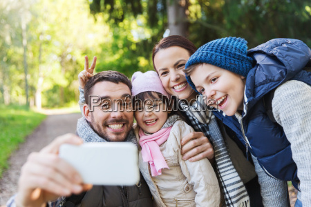 family with backpacks taking selfie by