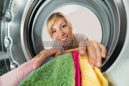 smiling woman inserting clothes in washing