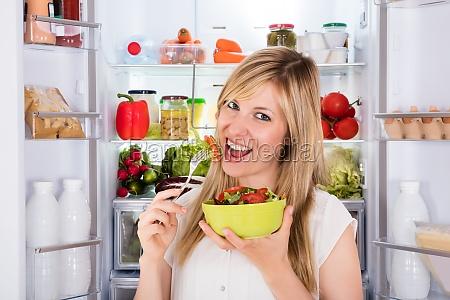 woman eating salad near refrigerator