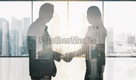 geschaeftspartner silhouetten handshake machen