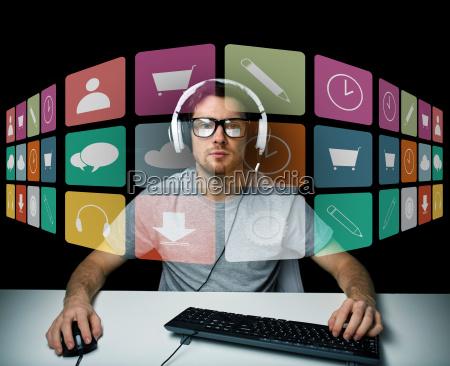mann im kopfhoerer mit computer und