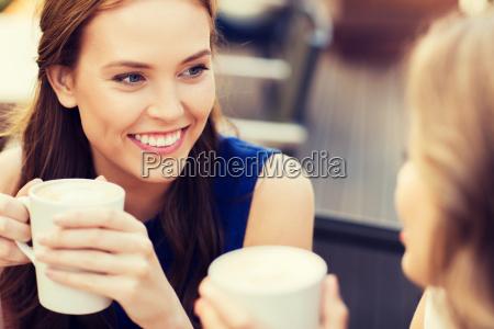 laechelnde junge frauen mit kaffeetassen im
