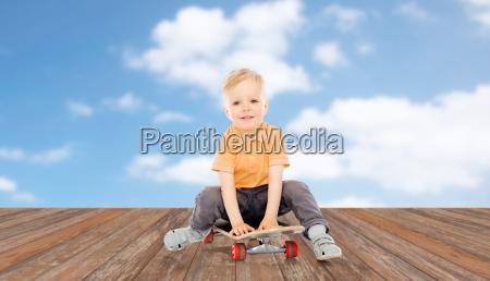 happy little boy sitting on skateboard