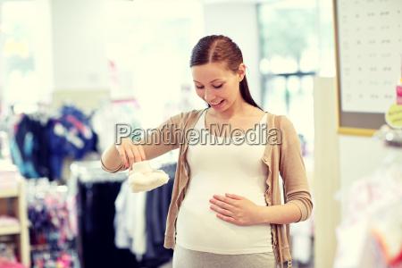 happy pregnant woman shopping at clothing