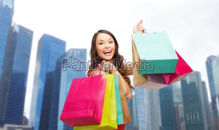 glueckliche frau mit einkaufstueten ueber singapur