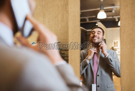 man calling on smartphone at clothing