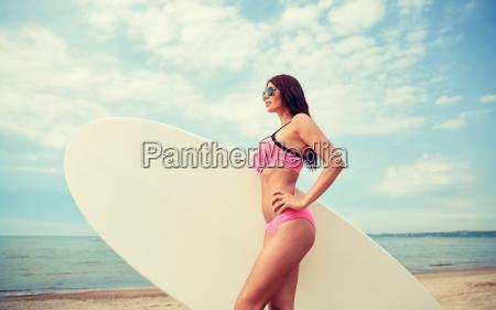 laechelnde junge frau mit surfbrett am