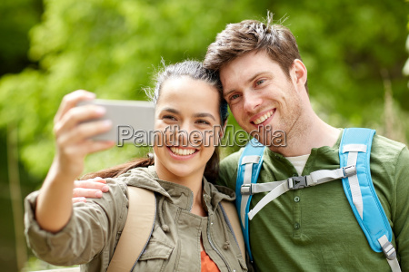 couple with backpacks taking selfie by