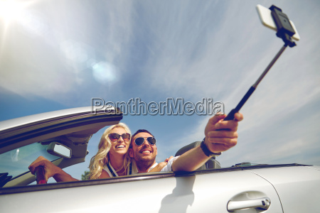 happy couple in car taking selfie