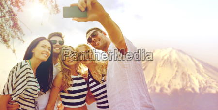 happy friends taking selfie by smartphone