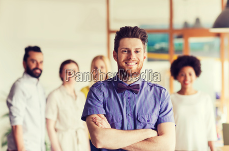gluecklicher junger mann ueber kreatives team