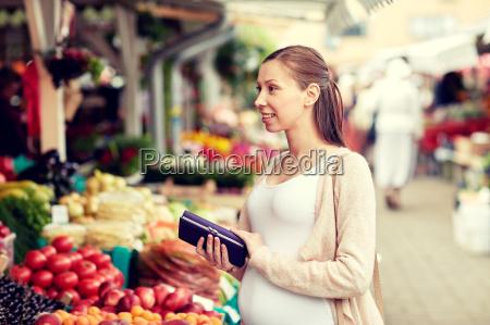 schwangere frau mit geldboerse kaufen lebensmittel