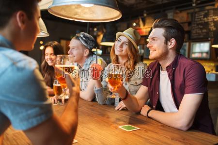 glueckliche freunde mit getraenken im bar
