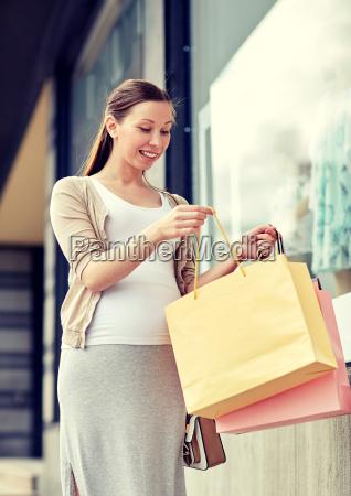 glueckliche schwangere frau mit einkaufstaschen in