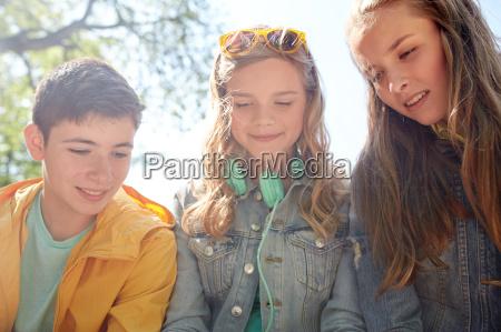 drei glueckliche teenager freunde kopfhoerer
