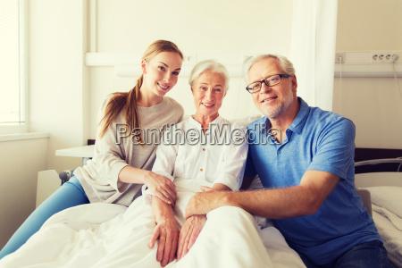 glueckliche familie besucht aeltere frau am