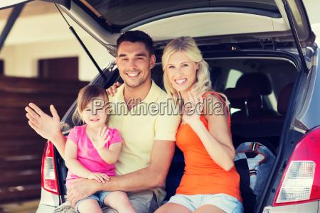 glueckliche familie mit fliessheck auto zu