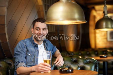 gluecklicher mann trinkt bier in der