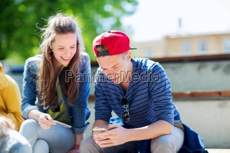 glueckliche jugendfreunde mit smartphones draussen