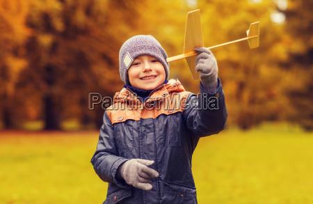 gluecklicher kleiner junge mit spielzeugflugzeug im