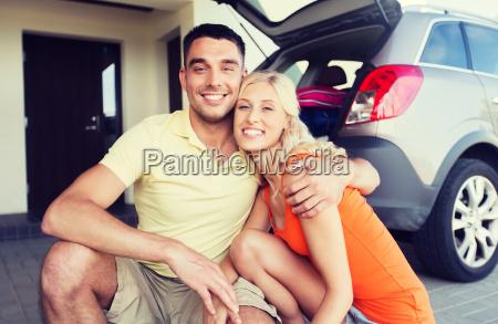 glueckliches paar umarmt auf dem auto