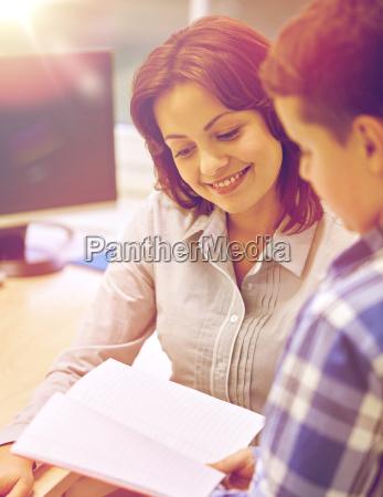 schule junge mit notizbuch und lehrer