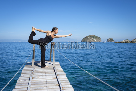 woman practicing yoga on small dock