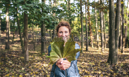 smiling woman holding autumn leaf in
