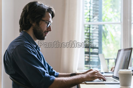 geschäftsmann, der, im, büro, arbeitend, am, laptop, sitzt - 20176803