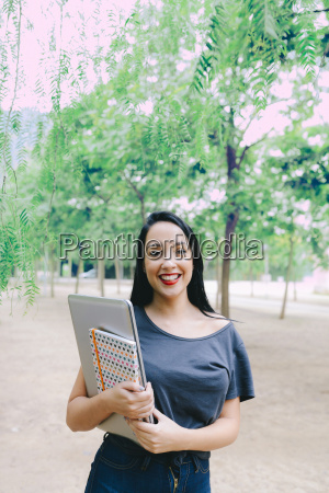 smiling young woman holding a laptop