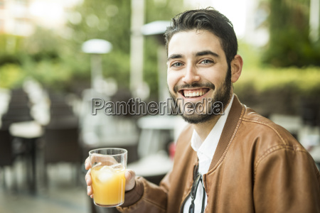 smiling man drinking juice at outdoor