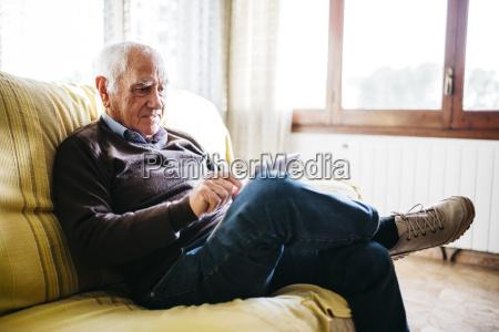 seniorenmann sitzt auf der couch mit