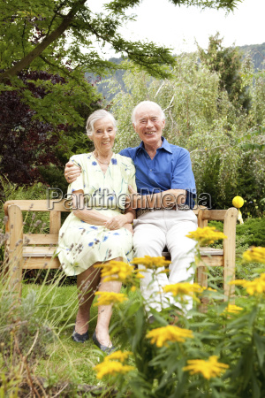 confident senior couple sitting on bench