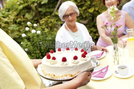mature woman serving cream cake in