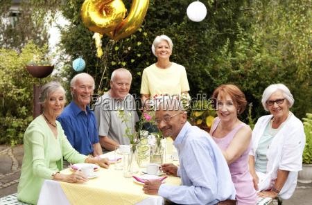 senior prople celebrating birthday in garden