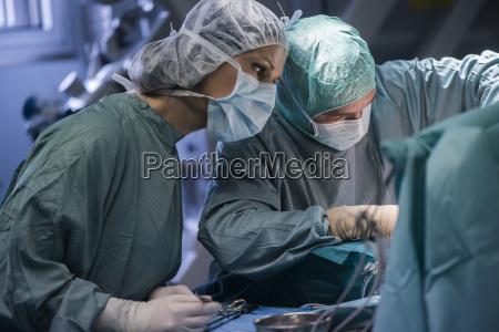 neurosurgeon with nurse closing operation wound