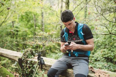 hiker looking on smartphone in nature