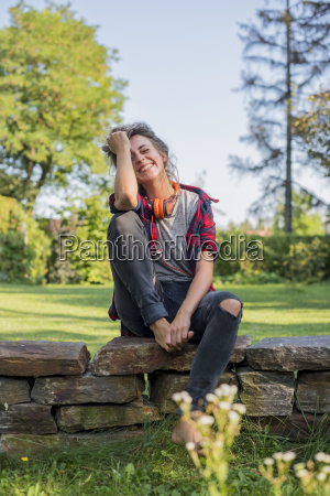 laughing young woman sitting on wall