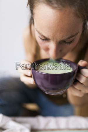 woman drinking matcha latte at home