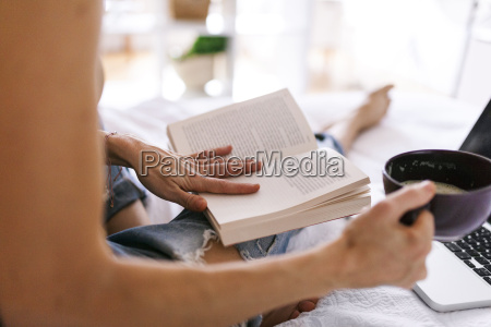 woman sitting on bed drinking coffee