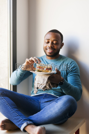 young man eating a club sandwich